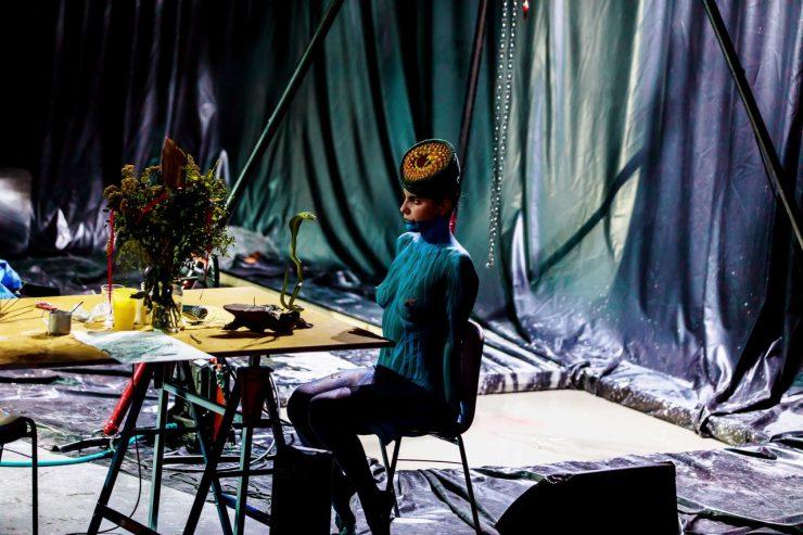 Na pierwszym planie stół z wieloma przedmiotami na blacie, siedzi przy nim naga kobieta, pomalowana ciemną farbą, w dziwnym, przypominającym toczek,nakryciu głowy. Na jej ciele widoczne są jaśniejsze, niebieskie, pionowe linie. Przed nią, na stole, znajduje się duży bukiet roślin i zielona, pionowa figurka kobry. W tle widoczna folia wyścielająca scenę i tworząca zasłonę, wrażenie bałaganu.