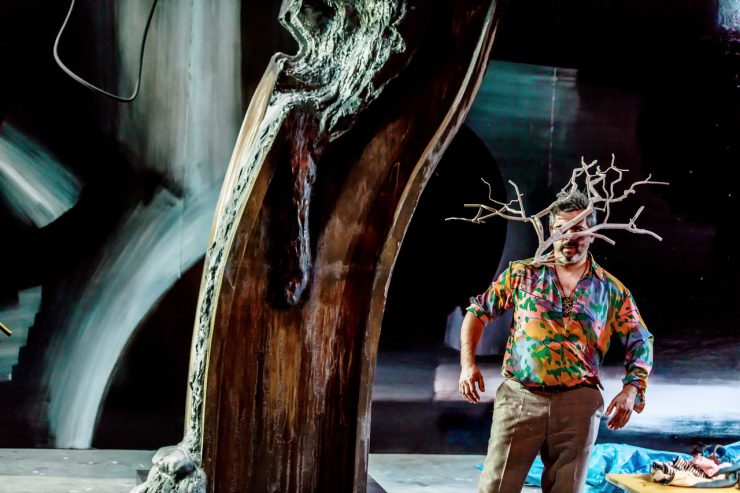 W centrum kadru element scenografii wyglądający jak gruby pień drzewa. Z prawej strony stoi przy nim mężczyzna w jaskrawej, kolorowej koszuli i beżowych spodniach. Na wysokości twarzy ma umocowaną bezlistną, białą gałąź.