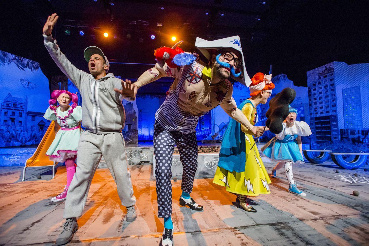 """W kolorowej, miejskiej scenografii widać pięć osób. Z obu stron są Córki, w dziewczęcych sukienkach, ta z lewej ma ciemnoróżowe włosy spięte w długie kucyki i literę """"B"""" naszytą na sukienkę, ta z prawej – niebieskie, z jednym kucykiem na czubku głowy i literę """"A"""" z przodu sukienki. W centrum znajduje się pirat, w kolorowym, wesołym stroju, ze sztucznymi tatuażami, trójkątnej czapce, z sumiastymi wąsami i w okularach. Na prawym ramieniu siedzi mu zabawkowa papuga. Z lewej strony pirata znajduje się Chłopak, w szarym dresie i czapce z daszkiem, krzyczy coś, prawą rękę ma wzniesioną do góry. Z prawej widać stojącą bokiem Mamę, w żółtej sukience i niebieskiej pelerynie. Trzyma w dłoni ciemną chmurkę na patyku."""