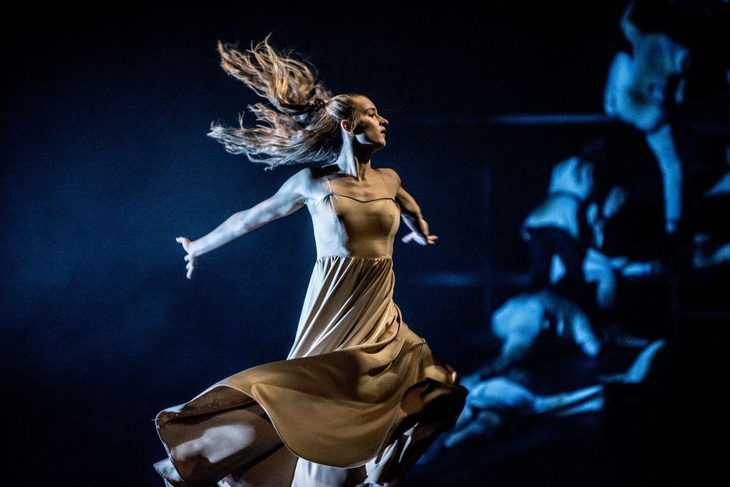 Dynamiczne ujęcie tańca kobiety w długiej jasnej sukni. Ma rozwiane, długie włosy, ręce skierowane są do tyłu, profilem zwrócona jest w prawą stronę. Z tyłu, w oddali, w ciemności widoczne są sylwetki ludzi.