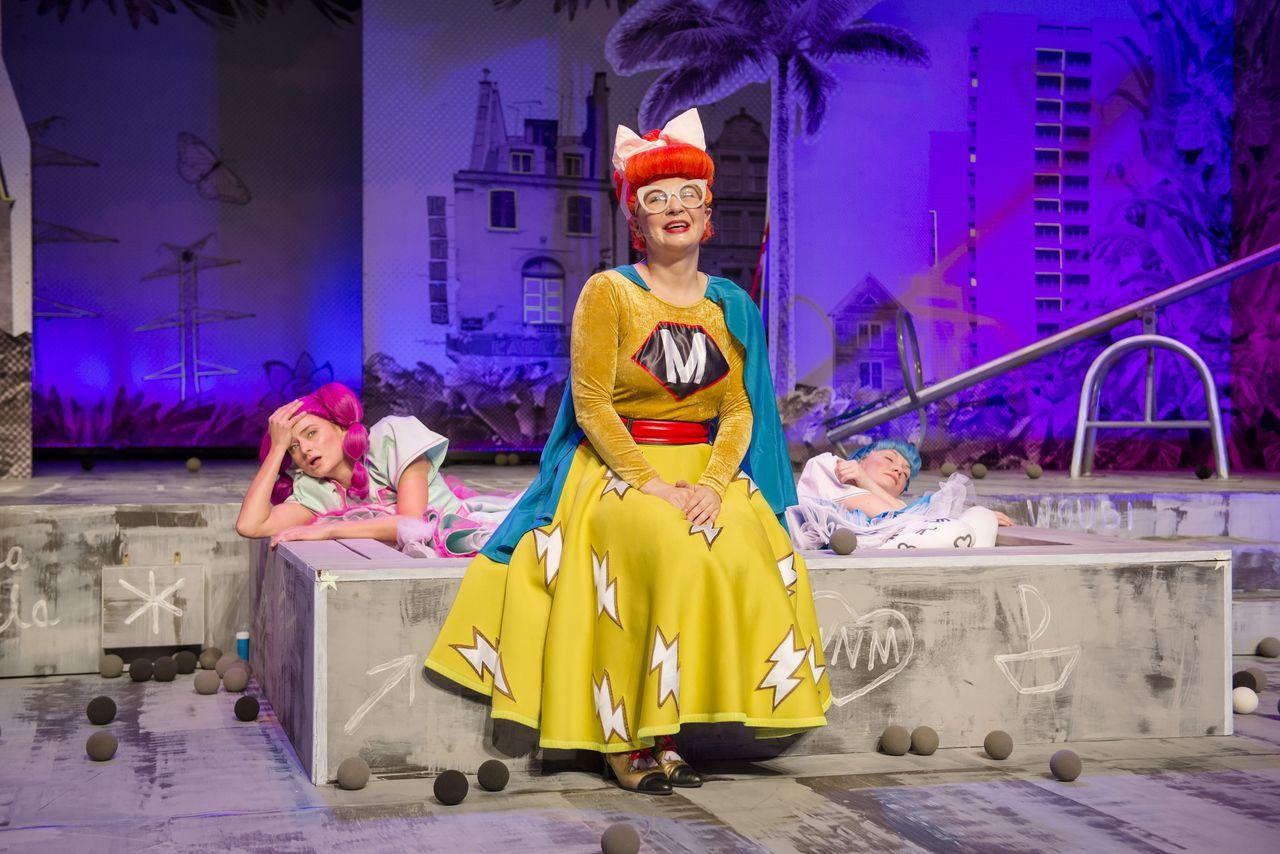 """Na brzegu szarej piaskownicy, wypełnionej piłeczkami, siedzi Mama. Ma na sobie żółtą spódnicę z wzorem błyskawicy, żółtą bluzkę z naszytą literką """"M"""", niebieską pelerynę, czerwony pasek, okulary w grubych, jasnych oprawkach. Rude włosy tworzą spory kok, przewiązany białą kokardą. Mama uśmiecha się i mówi coś, albo śpiewa. W piaskownicy znajdują się Córki, ta z prawej strony wygląda jakby spała, a ta z lewej trzyma głowę na zgiętej ręce, opiera się o brzeg piaskownicy."""