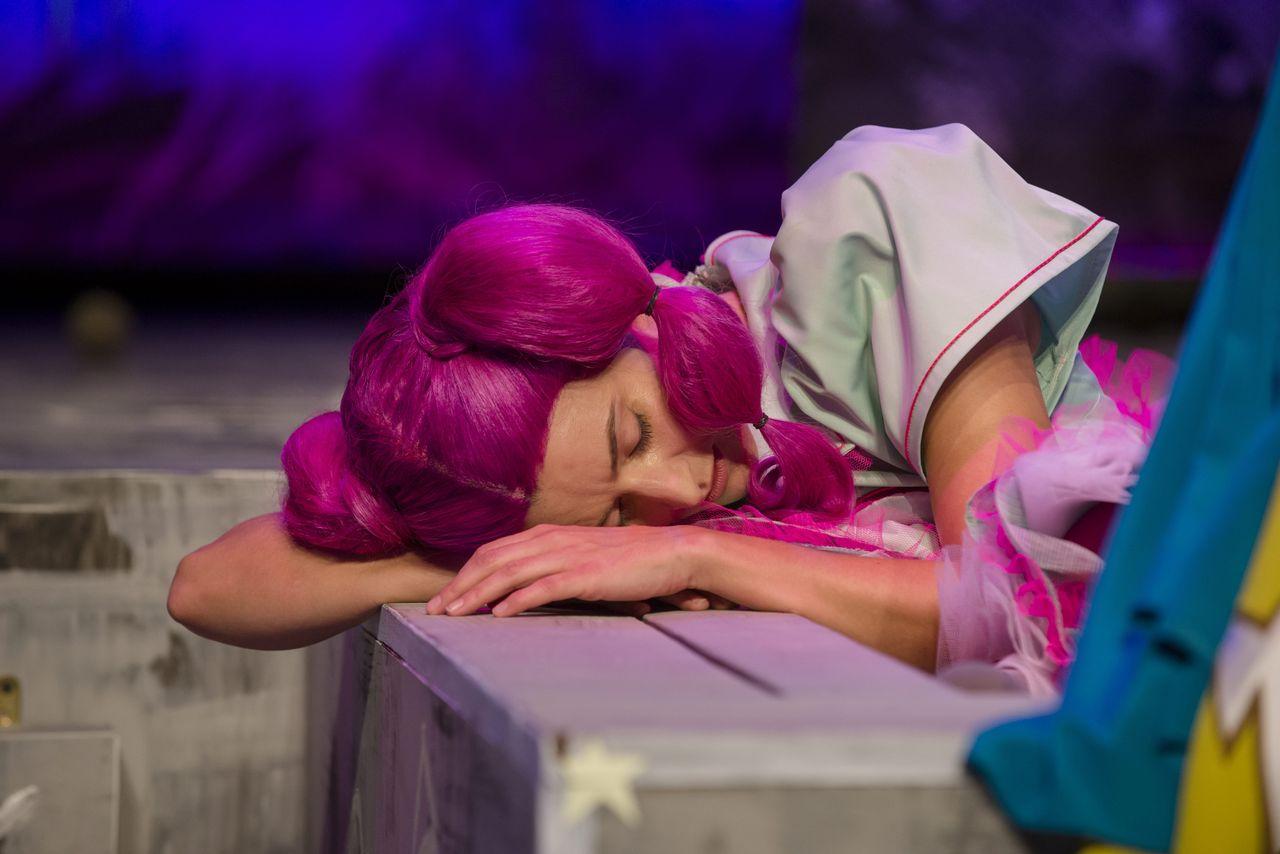Córka z ciemnoróżowymi włosami, w błękitnej sukience z bufiastymi rękawami, śpi opierając głowę na prawej, zgiętej ręce, ułożonej na brzegu piaskownicy.