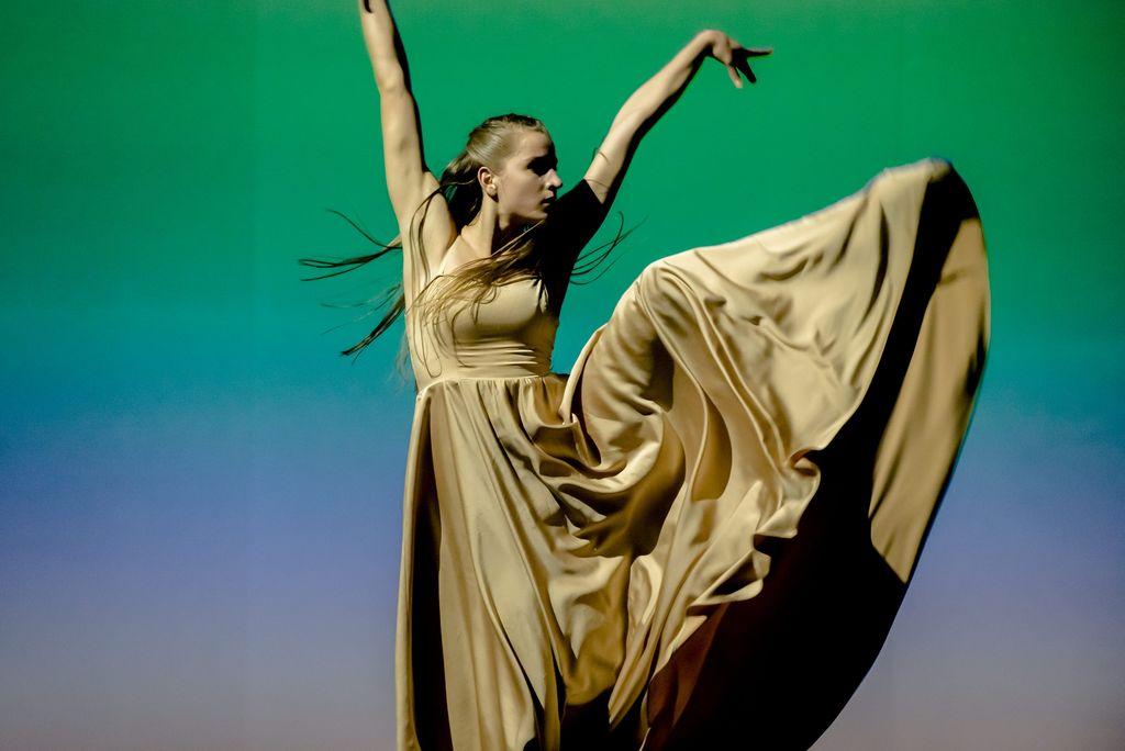 """Tancerka w długiej, jasnej sukni. Stoi na jednej, wyprostowanej nodze, drugą ma uniesioną bardzo wysoko. Ręce znajdują się w górze, są lekko rozłożone na boki, tworząc z tułowiem literę """"V"""". Dynamiczne ujęcie, włosy tancerki są długie i rozwiane. Tło od dołu ku górze zmienia kolor – od liliowego różu, przez jasnoniebieski po delikatną zieleń."""