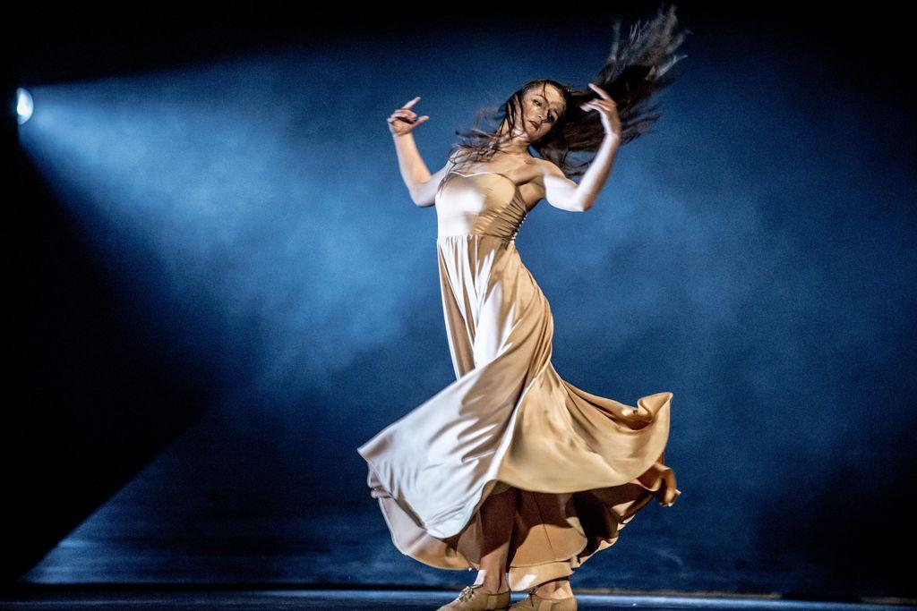 Tancerka w długiej, jasnej sukni, uchwycona w dynamicznej pozycji, w ruchu. Ręce ma uniesione, zgięte w łokciach, dłonie znajdują się na wysokości twarzy. Głowa lekko przechylona w tył, długie, rozwiane, ciemne włosy.