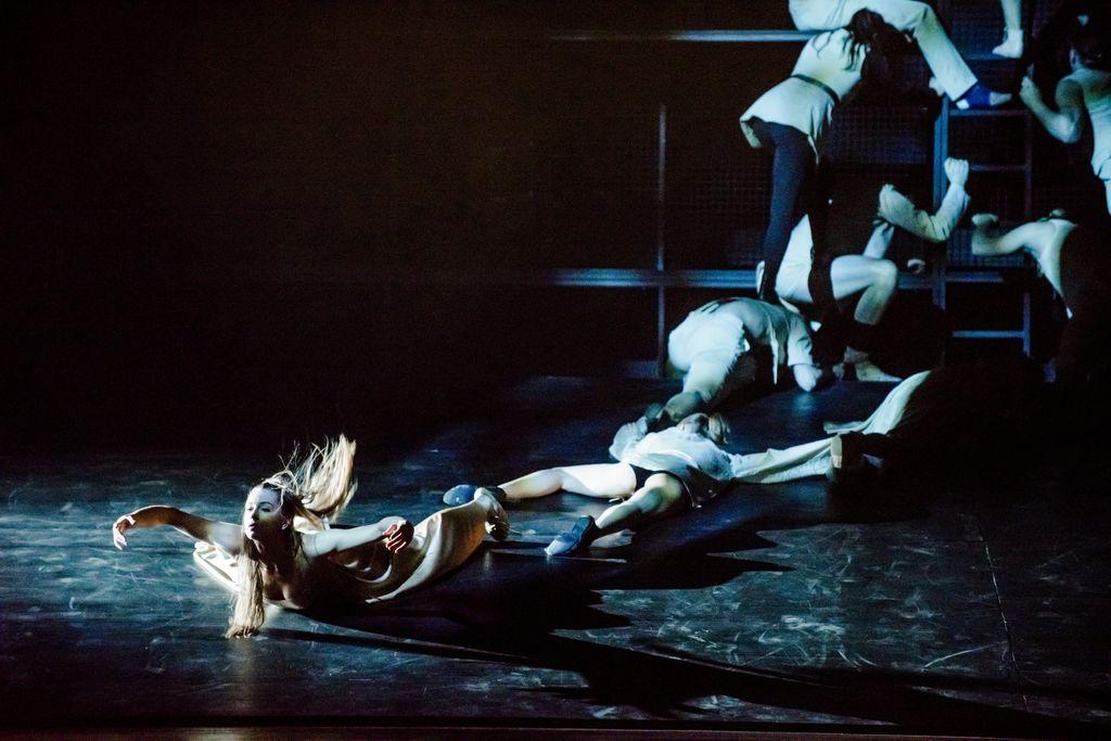 Dwie osoby leżą na wznak na podłodze, zwrócone stopami do siebie. Jedną z nich jest znajdująca się na pierwszym planie, z lewej strony, tancerka w jasnej sukni. Ma rozwiane, długie włosy, ręce rozłożone na boki, lekko uniesione nad podłogą, podobnie jak jej głowa i klatka piersiowa. Z prawej strony, w tle, kilka postaci wspina się wspina się na barierkę.