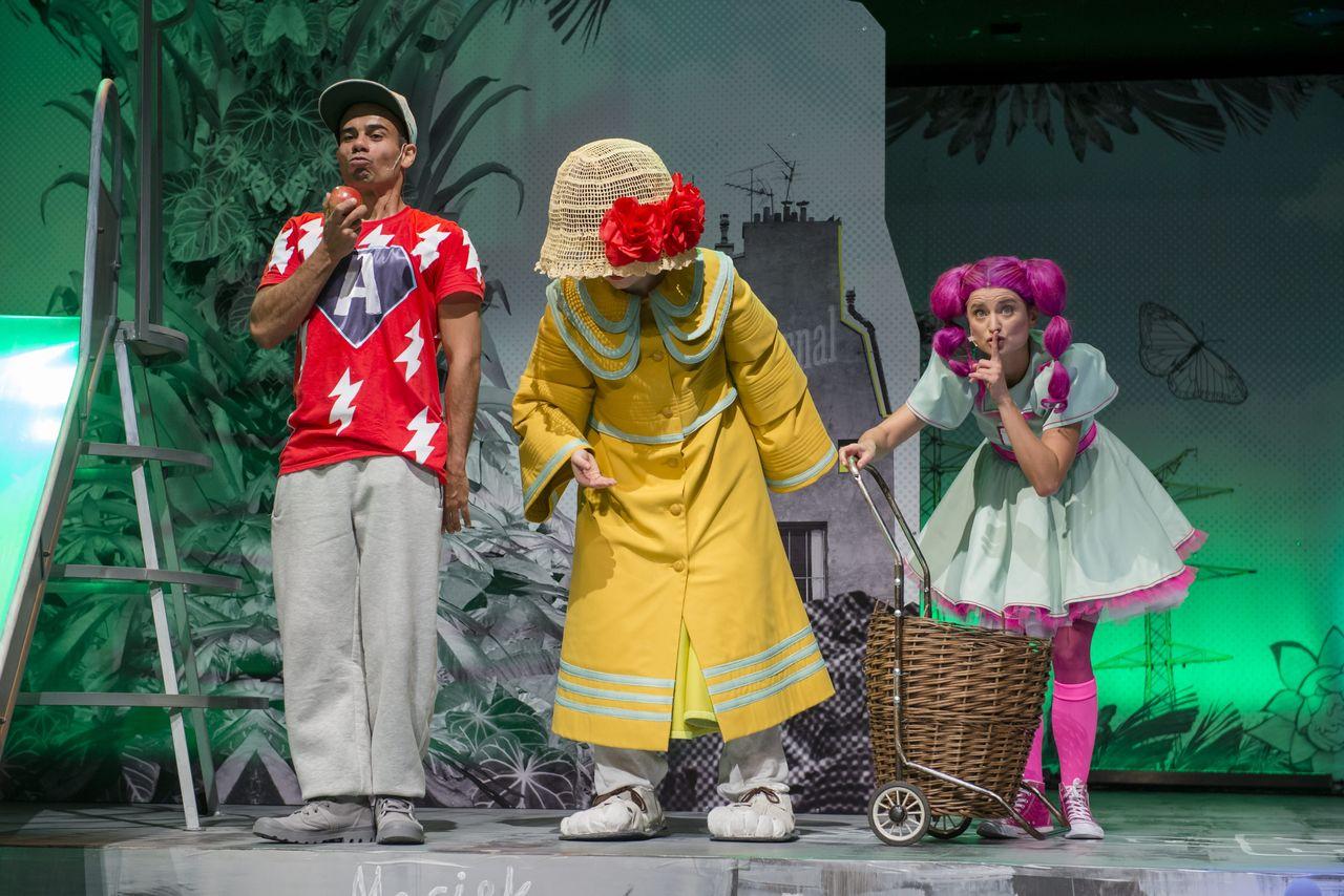 """Z lewej strony stoi Chłopak, ubrany w szare, dresowe spodnie, czerwoną koszulkę z literą """"A"""" i czapkę z daszkiem. W prawej dłoni podniesionej ku głowie, trzyma jabłko. Z prawej strony jest Córka z ciemnoróżowymi włosami, przykłada do ust palec wskazujący , w geście uciszania. Trzyma prawą ręką wiklinowy wózek zakupowy na kółkach. W środku znajduje się tajemnicza Babcia, z twarzą niewidoczną, bo zakrytą dużym kapeluszem. Ma na sobie żółty płaszcz, jest lekko pochylona."""