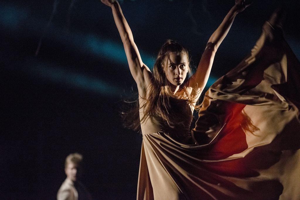 """Na pierwszym planie, z prawej strony znajduje się tancerka w długiej, jasnej sukni. Stoi na jednej, wyprostowanej nodze, drugą ma uniesioną bardzo wysoko. Ręce znajdują się w górze, są lekko rozłożone na boki, tworząc z tułowiem literę """"V"""". Dynamiczne ujęcie, włosy tancerki są długie i rozwiane."""