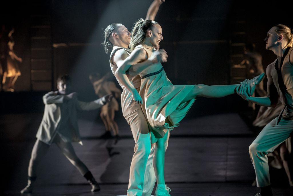 Na pierwszym planie troje tancerzy. Mężczyzna przytrzymuje odwróconą do niego tyłem kobietę pod pachami, jej prawa noga jest uniesiona i skierowana w stronę tancerza, który przytrzymuje prawą dłonią stopę tancerki. W tle widoczni inni tancerze, wykonujący dynamiczne ruchy.