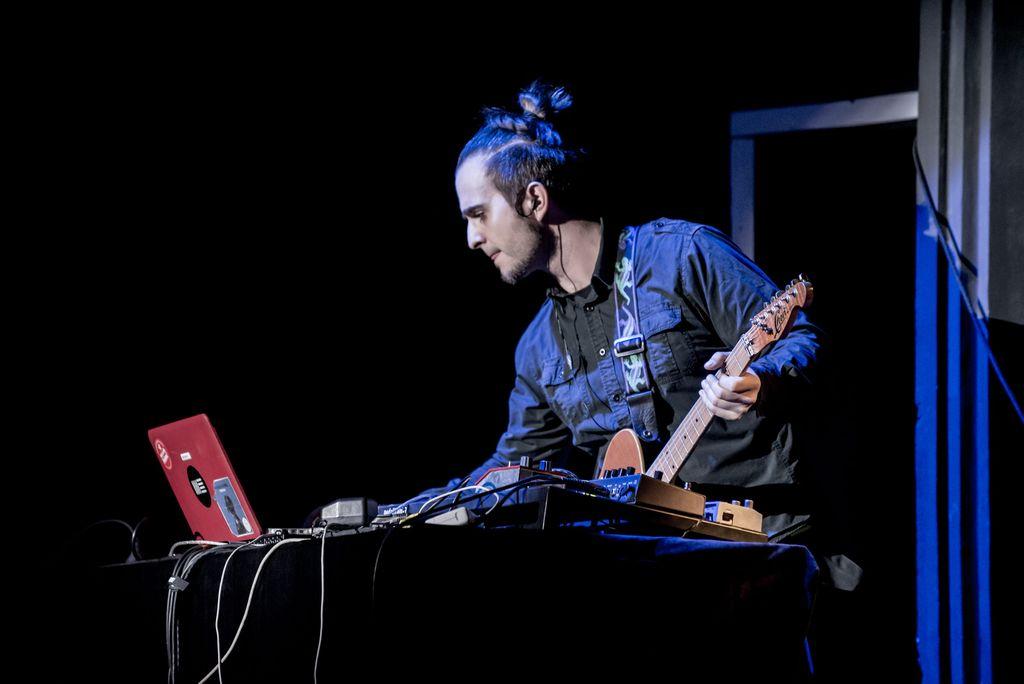 Muzyk z gitarą, trzymający jej gryf lewą dłonią, pochylony w stronę konsoli, na której znajduje się oprócz wielu urządzeń, także przenośny komputer. Mężczyzna stojący za konsolą, patrzy w kierunku ekranu komputera, jest ubrany w niebieską, dżinsową koszulę, włosy ma związane w kucyk na czubku głowy.