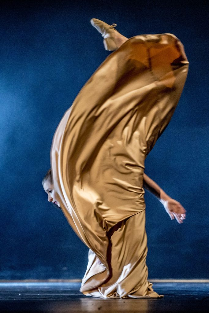 Tancerka w długiej sukni, stoi na jednej nodze, mocno pochylona w przód. Druga noga uniesiona jest bardzo wysoko. Dynamiczne ujęcie podkreśla udrapowana tkanina sukni, zasłaniająca całą sylwetkę tancerki.