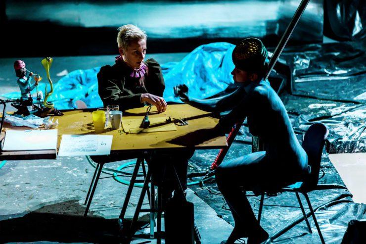 Przy stole siedzą dwie kobiety. Jedna - widoczna bokiem, naga, pomalowana ciemną farbą, w dziwnym, przypominającym toczek,nakryciu głowy. Druga, ubrana w ciemny strój, patrzy badawczo na nagą, mówi coś do niej, palcami prawej dłoni dotyka blatu stołu. W tle widoczna folia wyścielająca scenę, wrażenie bałaganu potęguje widok blatu stołu, na którym znajdują się różne przypadkowe przedmioty, na przykład figurka fakira z kobrą.