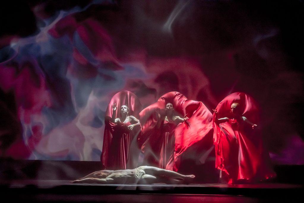 Nad leżącym na podłodze człowiekiem, stoją trzy kobiety ubrane w powiewne, czerwone szaty, tworzy się wokół ich sylwetek wrażenie silnego ruchu powietrza, unoszącego tkaniny. Tło jest rozjarzone czerwienią i fioletem, wygląda jakby postaci obejmował ogień i dym.