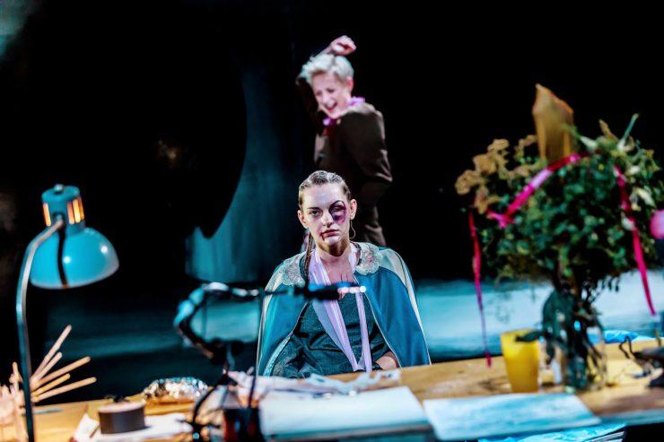 Przy stole siedzi smutna, młoda kobieta w niebieskim stroju, ze splecionymi włosami. Jest ucharkateryzowana na ofiarę przemocy, ma podbite, opuchnięte, lewe oko, przy prawym kąciku ust spływa strużka krwi. Z prawej strony, w nieostrości widoczny duży bukiet stojący na stole, z lewej – lampa biurkowa. Za siedzącą widać kobietę z jasnymi, krótkimi włosami, krzyczącą i unoszącą w górę prawą rękę.