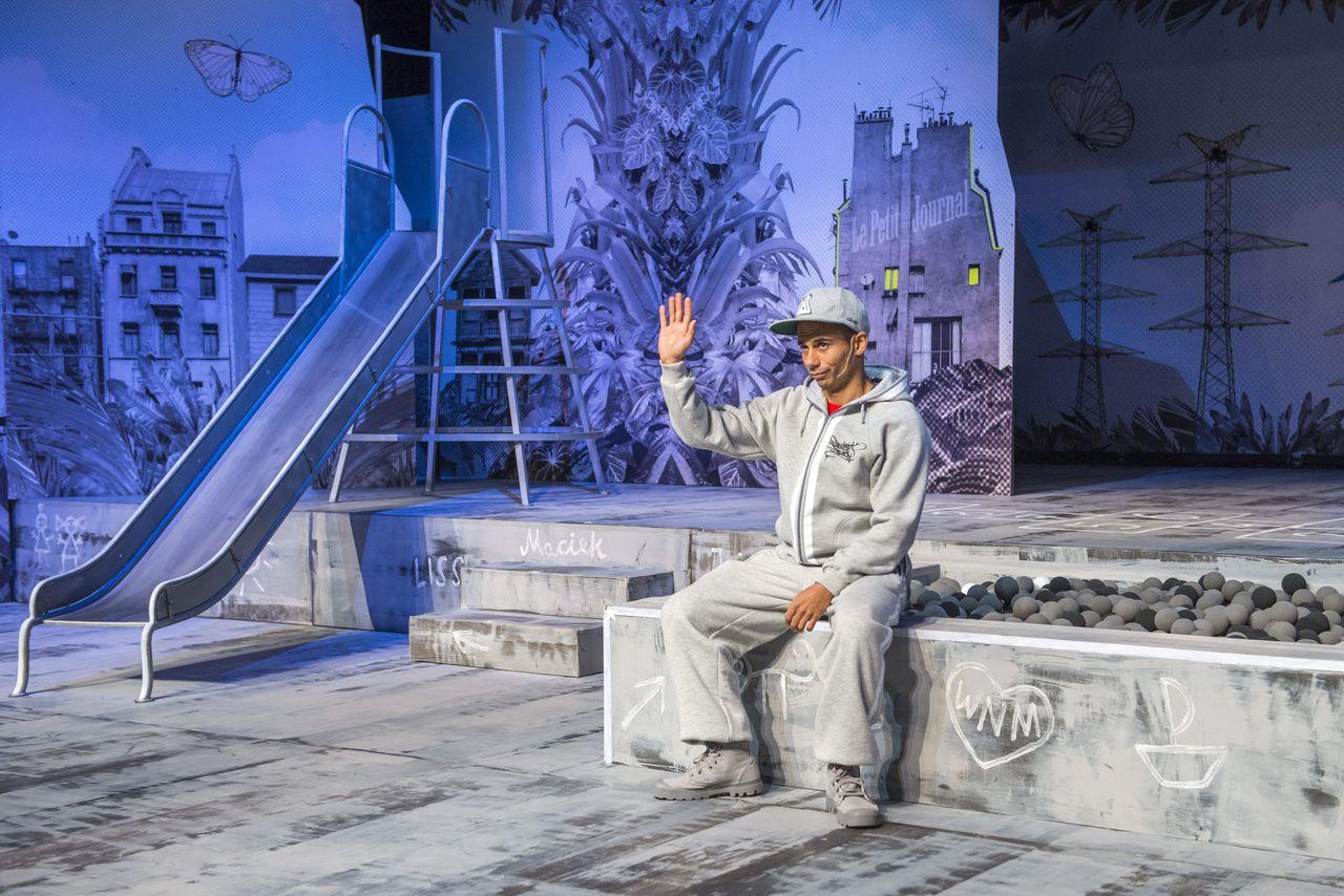 Na brzegu piaskownicy, która wraz z innymi urządzeniami tworzy scenerię placu zabaw, siedzi Chłopak w szarym dresie i czapce z daszkiem. Prawą, zgiętą rękę, trzyma uniesioną ku górze. W tle widoczna scenografia z obrazkami przedstawiającymi domy, rośliny, motyla, metalowe wieże.