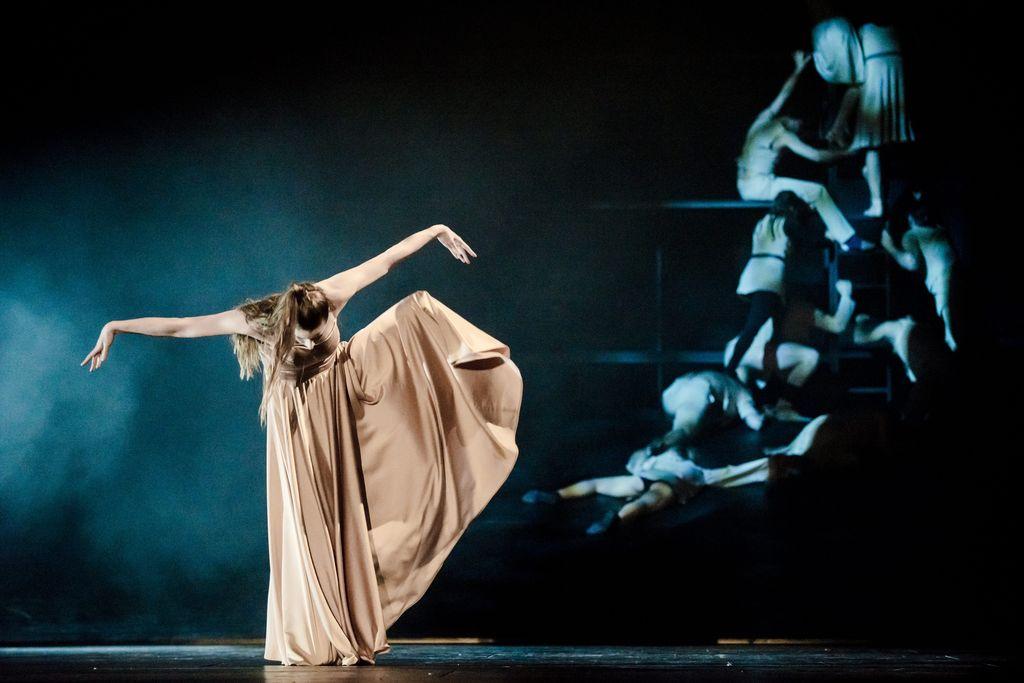 Tancerka w jasnej, długiej sukni. Stoi na wyprostowanej prawej nodze, lewą, zgiętą w kolanie, unosi wysoko nad ziemią. Tułów ma pochylony do przodu, w dół opadają jej długie, spięte włosy. Ręce są wyprostowane w obie strony, z dłońmi skierowanymi w dół. Z prawej strony, w tle, niewyrażnie widoczne inne osoby – leżące i wspinające się na barierkę.