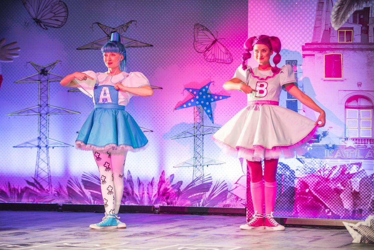"""Na tle scenografii z grafikami metalowych konstrukcji, motyli, gwiazd, budynków i roślin, oświetlonej miłym, liliowym i różowym światłem, stoją obie Córki. Z lewej - ta w niebieskiej sukience i z niebieskimi włosami, z literą """"A"""" z przodu sukienki, z prawej - w pastelowej, różowej sukience, z ciemnoróżowymi włosami i z literą """"B"""" naszytą na sukienkę. Są uśmiechnięte, palcami prawych rąk wskazują na przód sukienek z naszytymi literami."""