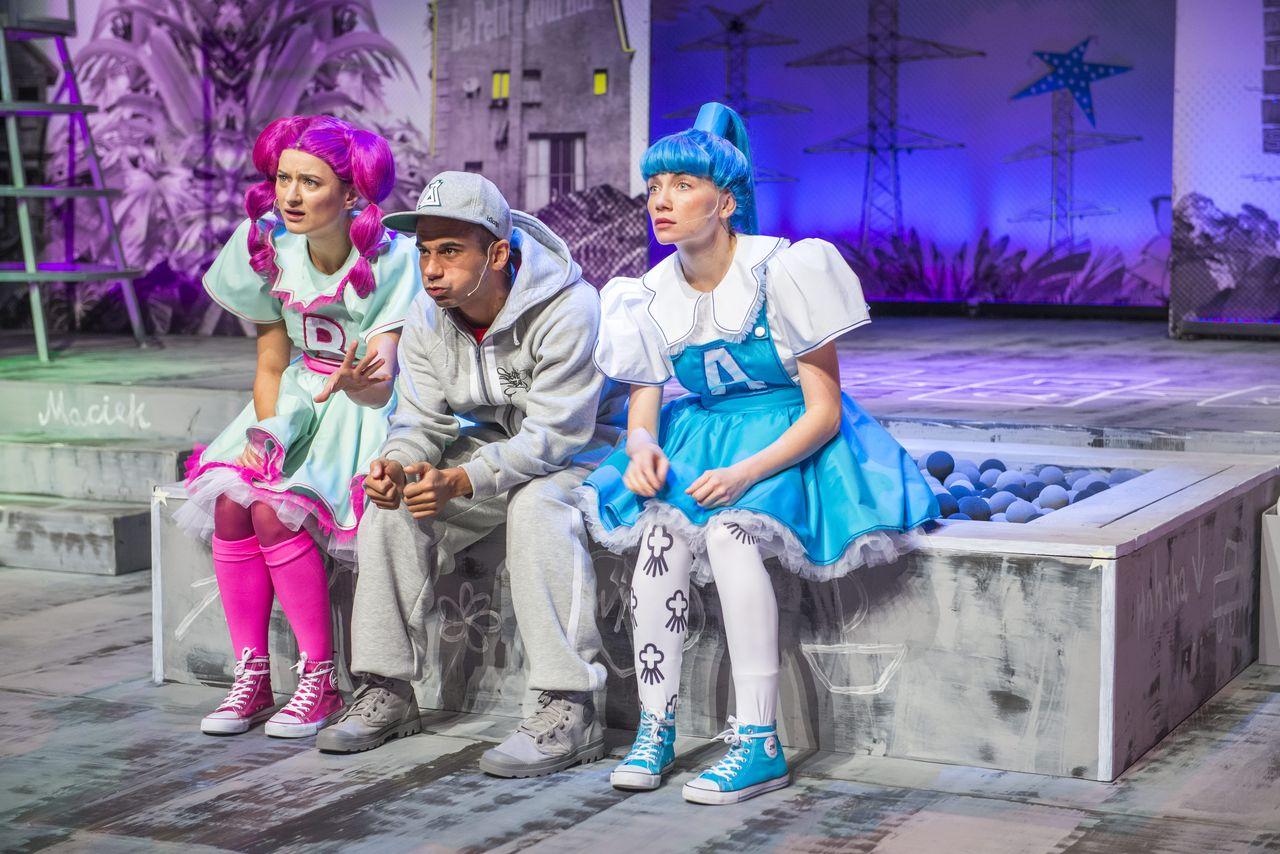 """Na obramowaniu piaskownicy wypełnionejniebieskimi piłeczkami siedzą trzy osoby. Z lewej - Córka z literą """"B"""" z przodu sukienki, na środku - Chłopak, w szarym dresie i czapce z daszkiem, a z prawej - Córka z literą """"A"""" na sukience. Patrzą w tym samym kierunku, z zaciekawieniem i zdumieniem."""