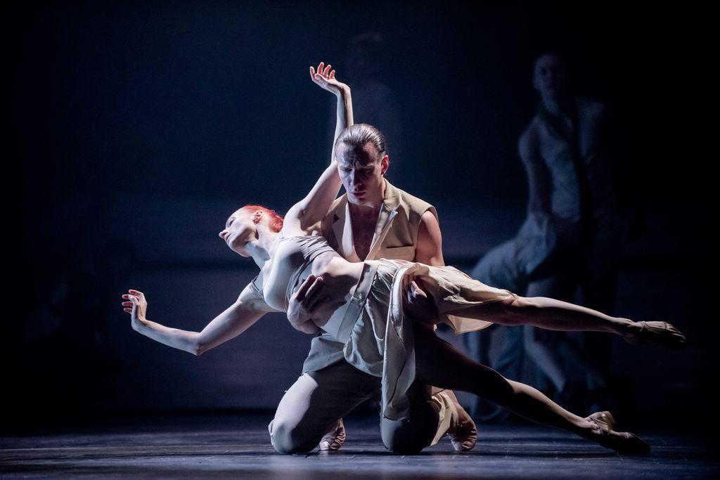 Dwoje tancerzy w jasnych strojach. Mężczyzna klęczy, przytrzymuje odwróconą tyłem do siebie tancerkę, znajdującą się w niemal poziomej pozycji. Unosi ją lekko ponad sceną. Tło jest ciemne, w oddali, z prawej strony widać sylwetki innych osób.