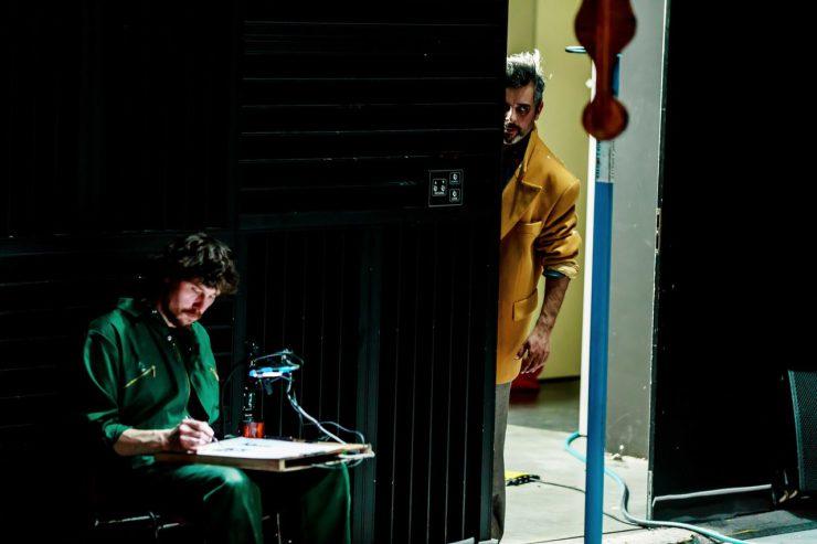 Z lewej strony kadru, na ciemnym tle, widoczny ciemnowłosy, siedzący mężczyzna z brodą i wąsami. Ma na sobie ciemnozielony strój, w prawej dłoni trzyma przedmiot, którym rysuje, lub maluje na oświetlonej płaszczyźnie, którą trzyma na kolanach. Z prawej strony, w jasnym prześwicie, stoi drugi mężczyzna, widać połowę jego ciała. Ma nastroszone włosy, patrzy złowieszczo w prawą stronę, ubrany jest w żółtą marynarkę i jasne spodnie.