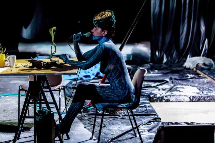 Na pierwszym planie długi stół z wieloma przedmiotami na blacie, siedzi przy nim widoczna bokiem, naga, pomalowana ciemną farbą, w dziwnym, przypominającym toczek,nakryciu głowy. Na jej ciele widoczne są jaśniejsze, niebieskie, pionowe linie. W prawej dłoni trzyma mikrofon, mówi do niego lub śpiewa. Patrzy w stronę zielonej, pionowej figurki kobry, znajdującej się na stole. W tle widoczna folia wyścielająca scenę i tworząca zasłonę, wrażenie bałaganu.