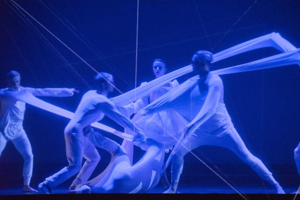 Scena oświetlona niebieskim światłem. Kilkoro tancerzy tworzy grupę zaplątaną w pasy tkanin, utworzone przez długie rękawy białych strojów, w jakie są ubrani.