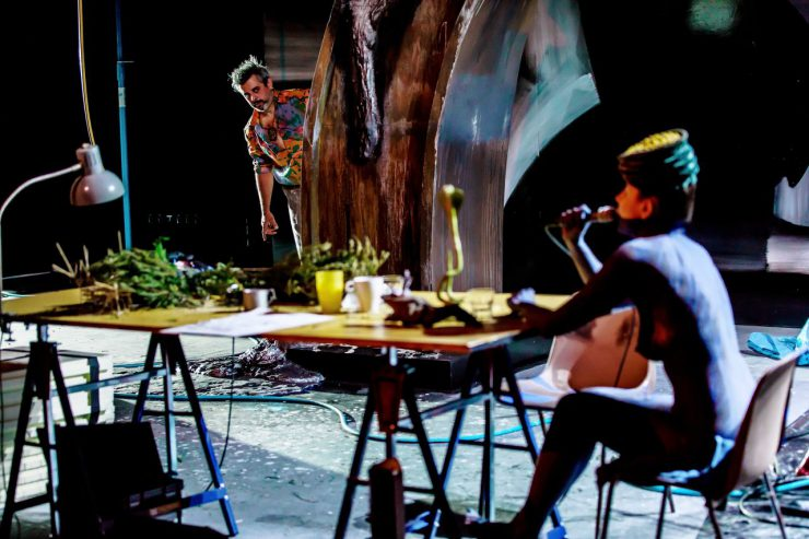 Na pierwszym planie długi stół z wieloma przedmiotami na blacie, siedzi przy nim widoczna bokiem, naga, pomalowana ciemną farbą kobieta w nakryciu głowy, trzyma w prawej dłoni mikrofon. Jej sylwetka, podobnie jak stół, są rozmyte. Z oddali przygląda się kobiecie, wychylający się zza elementu scenografii człowiek. Mężczyzna w jaskrawej, kolorowej koszuli, ma brodę i wąsy oraz zmierzwione, postawione w górę włosy.