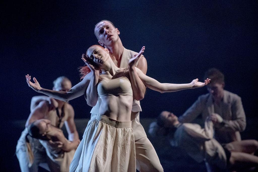Na pierwszym planie dwoje tancerzy w jasnych strojach. Mężczyzna przytrzymuje tancerkę, ułożywszy zgięte w łokciach ręce pod jej pachami. Kobieta ma ramiona rozłożone na boki, głowę lekko przechyloną, zamknięte oczy. W tle widać dwie pary tancerzy.