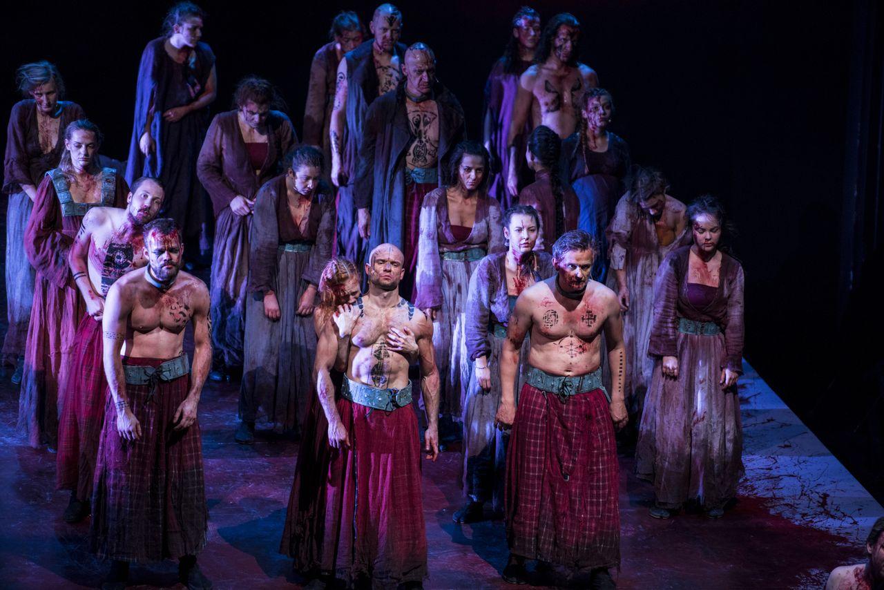 Grupa kilkunastu mężczyzn i kobiet stoi w czterech rzędach. Są zakrwawieni, niektórzy mężczyźni – półnadzy, ich szaty są sfatygowane, w kolorach fioletu, czerwieni, bordo. Większość ma ręce opuszczone bezwładnie wzdłuż ciała. Do pleców mężczyzny stojącego w pierwszym rzędzie przywiera płacząca kobieta.