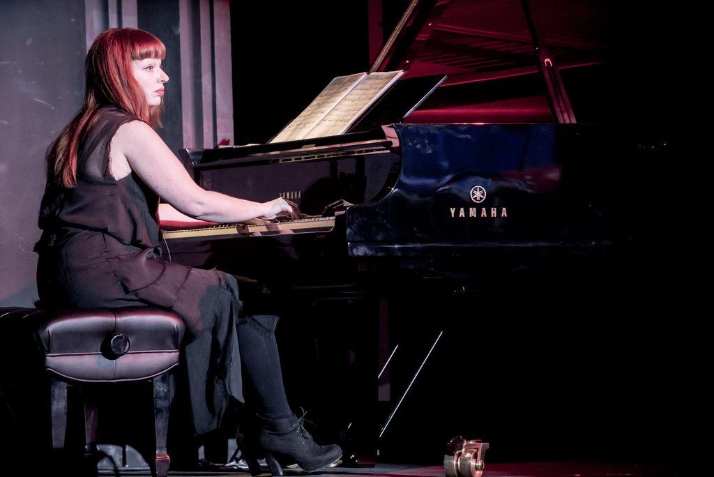Z lewej strony siedzi przy fortepianie pianistka. Ma długie, rude włosy, bladą twarz z lekkim makijażem, czerwone, pełne usta. Ubrana jest w ciemną sukienkę, ciemne rajstopy, na stopach ciemne, zabudowane buty. Profilem zwrócona jest w prawą stronę, dłonie trzyma na klawiaturze, przed nią leżą nuty.