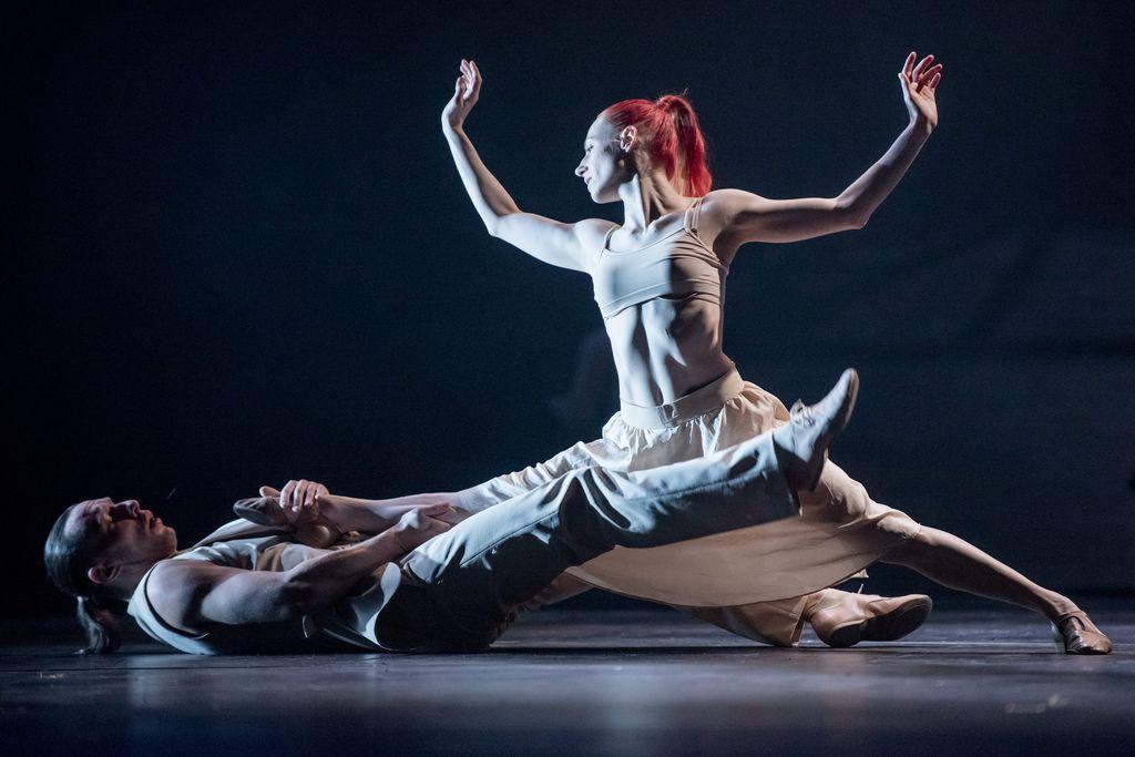 Duet tancerzy w jasnych, lekkich strojach. Mężczyzna z lewej strony w pozycji półleżącej, na wznak, przytrzymuje prawą stopę tancerki, która w szpagacie znajduje się nad nim, oparta lewą stopą na ziemi. Kobieta unosi obydwie ręce ku górze, skierowana jest profilem ku mężczyźnie, ma rude włosy, związane w kucyk.