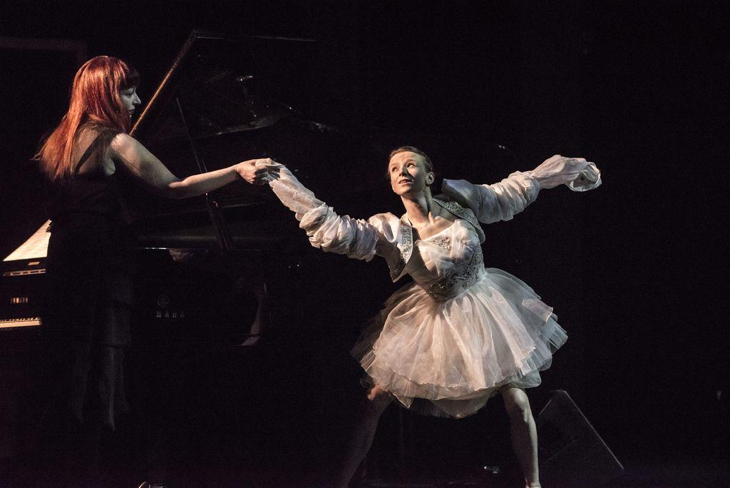 Dwie kobiety na pierwszym planie. Z lewej strony, przy fortepianie, stoi pianistka. Ma długie, rude włosy,ciemną sukienkę. Profilem zwrócona jest w prawą stronę, wyciąga rękę w kierunku tancerki. Lekko pochylona tancerka stoi w rozkroku, dotyka ręką dłoni pianistki. Ubrana jest w białe bolerko z bardzo długimi rękawami i sukienkę z gorsetem, z rozkloszowaną, tiulową spódnicą sięgającą kolan.