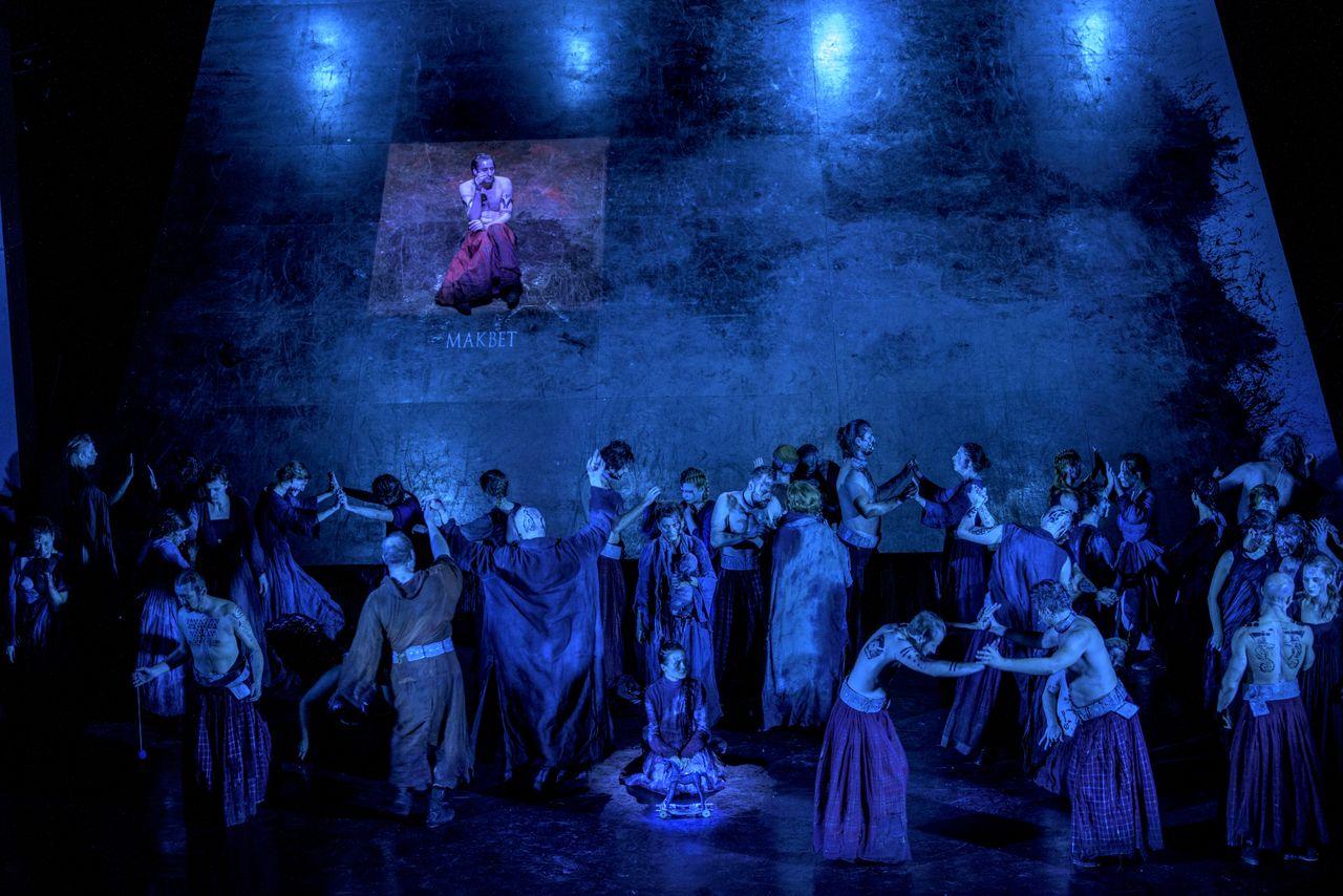 Na scenie znajduje się duża grupa ludzi, mężczyzn i kobiet, półnagich i w tradycyjnych, szkockich strojach. Za nimi, duża podnoszona płaszczyzna sceny, tworzy jakby ścianę. Na niej, ustawionej niemal w pionie, przysiadł Makbet. Wszystkich spowija niebieskie światło. W centrum grupy siedzi przy drewnianym koniku lady Makbet.