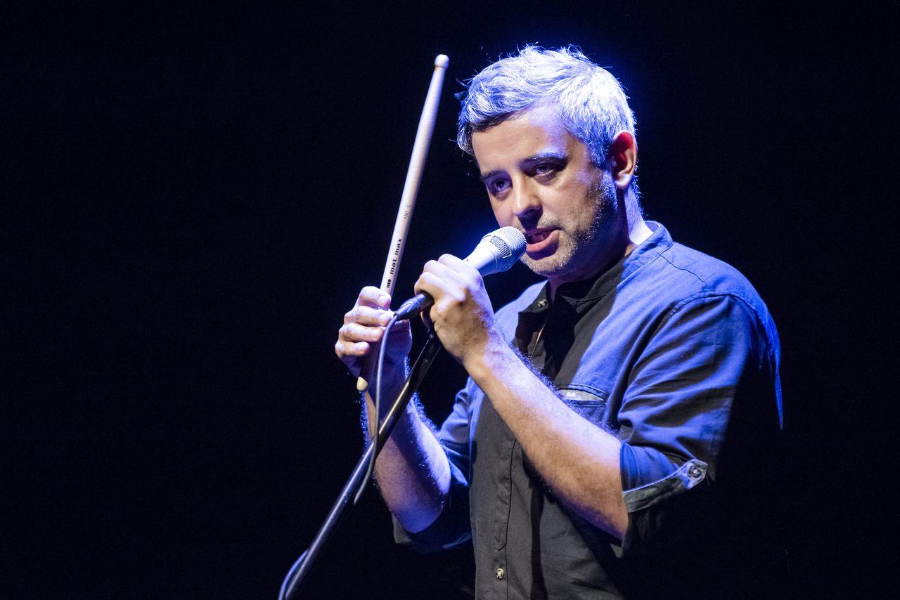 Konrad Imiela, lekko oświetlony niebieskim światłem, śpiewa do mikrofonu na statywie. Lewą reką przytrzymuje mikrofon, prawą unosi do góry pałeczkę do perkusji.