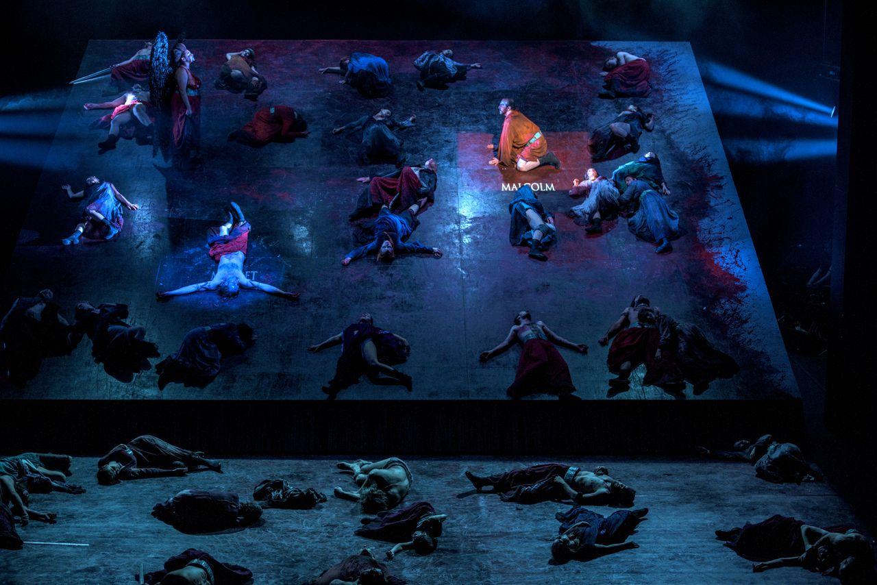 Duża grupa ludzi, część z nich leży na podnoszonej płaszczyźnie sceny tworzącej niemal pionową ścianę, a część z nich leży na dole, na właściwej scenie. Wśród nich, u góry podświetlone są postaci Malcolma i Makbeta, jedyną stojącą tam osobą jest Hekate. Podniesioną scenę pokrywa farba stylizowana na krew.