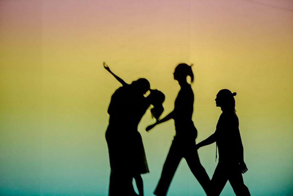 Trzy postaci przedstawione jak w teatrze cieni, dwie połączone ze sobą w tanecznym geście, jedna idzie w ich stronę, widać jej cień odbijający się na tle. Tło ma kolorystykę pasów zieleni, żółci i różu, przechodzących łagodnie w siebie.