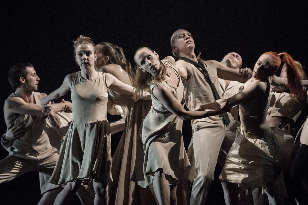 Grupa tancerzy, kobiet i mężczyzn w jasnych, lekkich strojach. Tworzą taneczne figury trzymając się po dwie, trzy osoby za ręce.