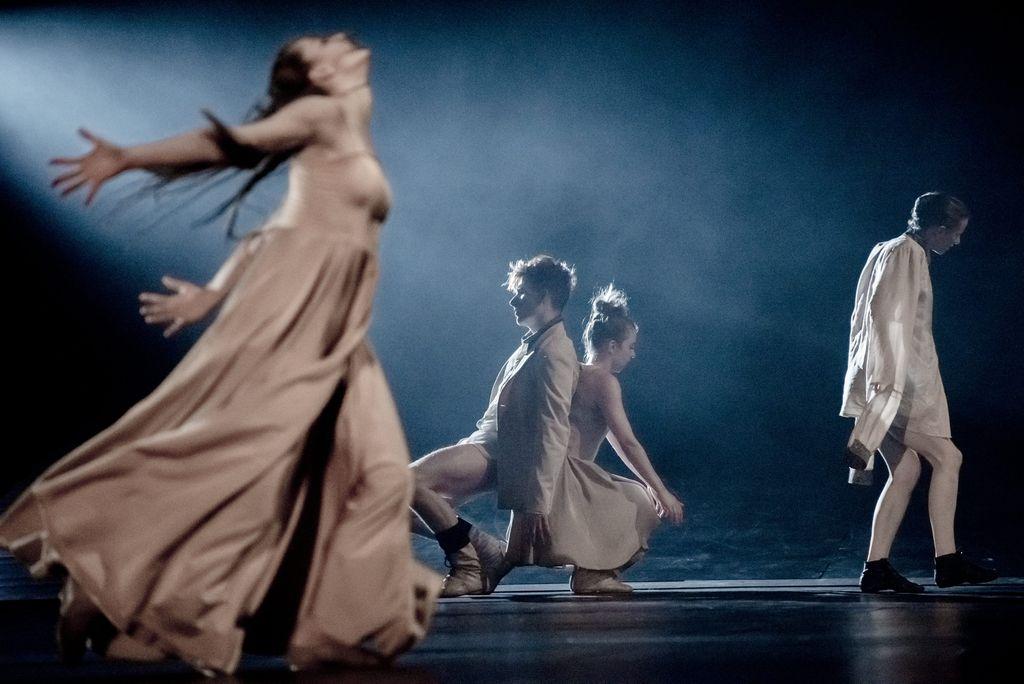 Z lewej strony kobieta w długiej sukni, w dynamicznym geście, na środku przysiada dwoje tancerzy odwróconych do siebie plecami, z prawej strony stoi tancerka w białej koszuli z bardzo długimi rękawami.