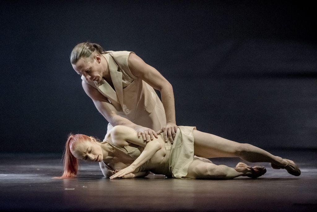Duet tancerzy, ubranych w jasne, lekkie stroje. Kobieta leży na prawym boku, lewą ręką dotyka ziemi, twarz ma zwróconą w dół. Mężczyzna klęczy pochylony nad nią, patrzy w jej stronę, prawą dłonią dotyka jej ręki, lewą trzyma na biodrze tancerki.