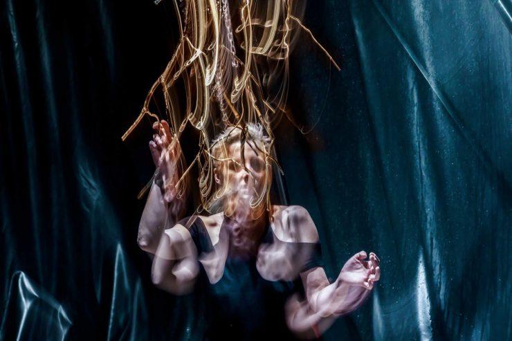 Postać kobiety na niebieskim tle, widoczna od pasa w górę. Twarz jest rozmyta, podobnie jak ręce, których ruch został uchwycony jako zwielokrotnienie obrazu. Nad głową kobiety gałązki, które tworzą jakby płonący obiekt.