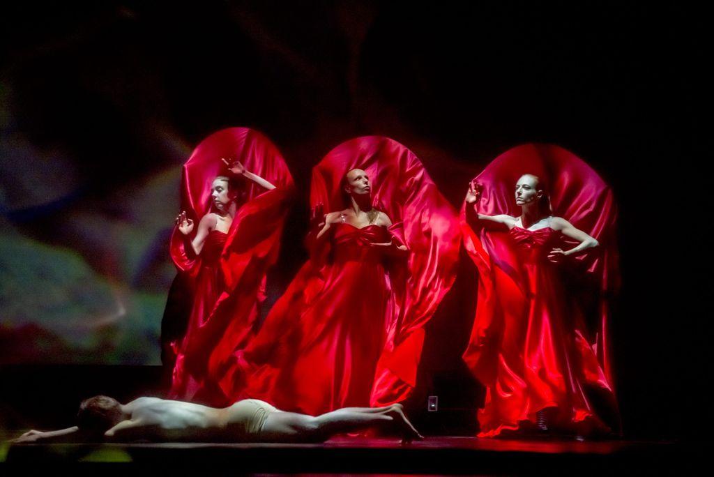 Nad leżącym na brzuchu człowiekiem, stoją trzy kobiety ubrane w powiewne, czerwone szaty, tworzy się wokół ich sylwetek wrażenie silnego ruchu powietrza, unoszącego tkaniny. Tło za nimi jest ciemne, mroczne.