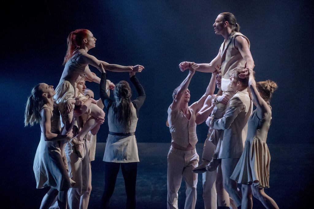 Dwie grupki osób w jasnych, lekkich strojach. Kilkoro kobiet i mężczyzn z lewej strony, unosi siedzącą na ich ramionach tancerkę. Taka sama grupka z prawej strony niesie tancerza. Oboje patrzą na siebie, ich ręce skierowane są ku sobie.