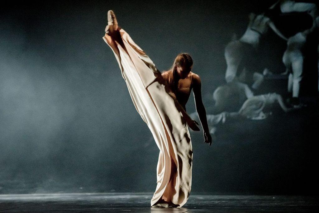 Tancerka w długiej jasnej sukni. Stoi na wyprostowanej lewej nodze, tułów i ręce są lekko przechylone w jej stronę. Druga wyprostowana noga jest uniesiona bardzo wysoko. Ciemnoniebieskie, lekko rozświetlone tło, z prawej strony majaczy grupka osób.