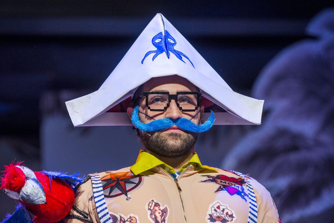 Zbliżenie na twarz Pirata, mężczyzny w okularach, który w innych scenach jest Drzewem, Księżycem, Tatą, Olbrzymem. Ma na głowie trójkątną czapkę z ośmiornicą, imitacje tatuaży na cielistym kostiumie, sumiaste niebieskie wąsy, na jego prawym ramieniu siedzi kolorowa, zabawkowa papuga.