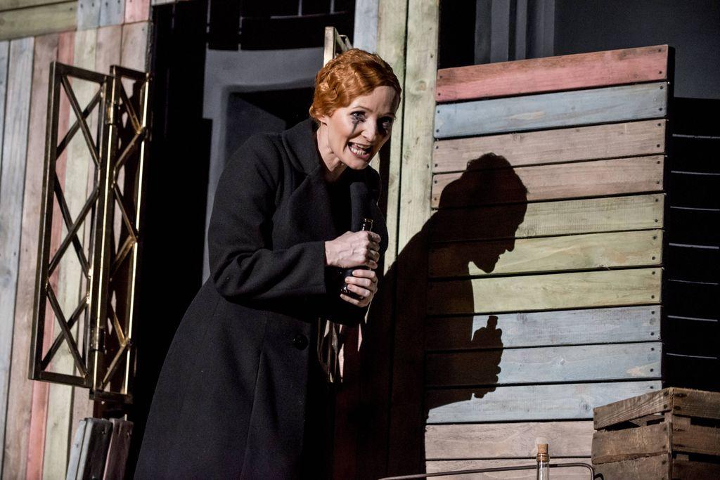 Kobieta na tle drewnianej konstrukcji i metalowej ramy okiennej. Ubrana w czarny płaszcz, ma spięte rude włosy, bladą twarz i rozmazany makijaż oczu. Trzyma w obu doniach otworzoną, ciemną butelkę. Śpiewa lub mówi, na drewnianej ścianie odbija się jej cień.