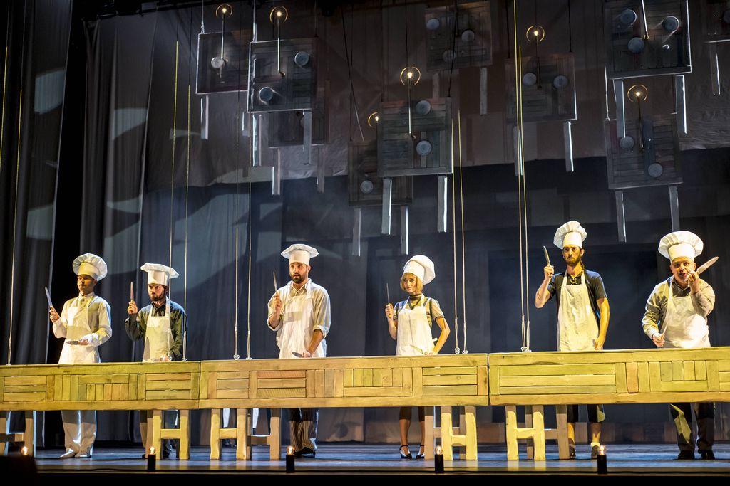 Długi drewniany, jasny stół, z blatem ciągnącym się wzdłuż całej sceny. Za nim stoi sześć osób, pięciu mężczyzn i jedna kobieta, w fartuchach i czapkach kucharskich, trzymają w uniesionych dłoniach noże. W tle wiszące u góry atrapy stołów.