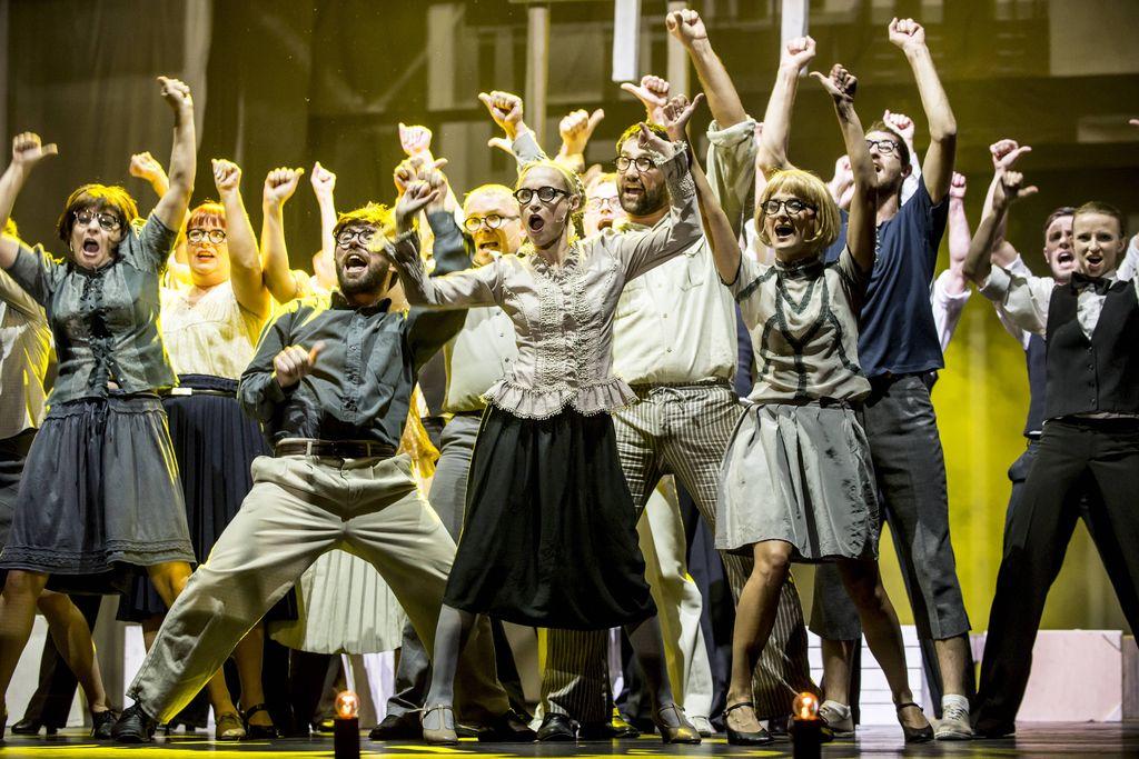 Grupa tańczących i śpiewających osób, w codziennych, zwykłych strojach. Kobiety i mężczyźni, prawie wszyscy w okularach, stoją w rozkroku, mają uniesione ku górze ręce.
