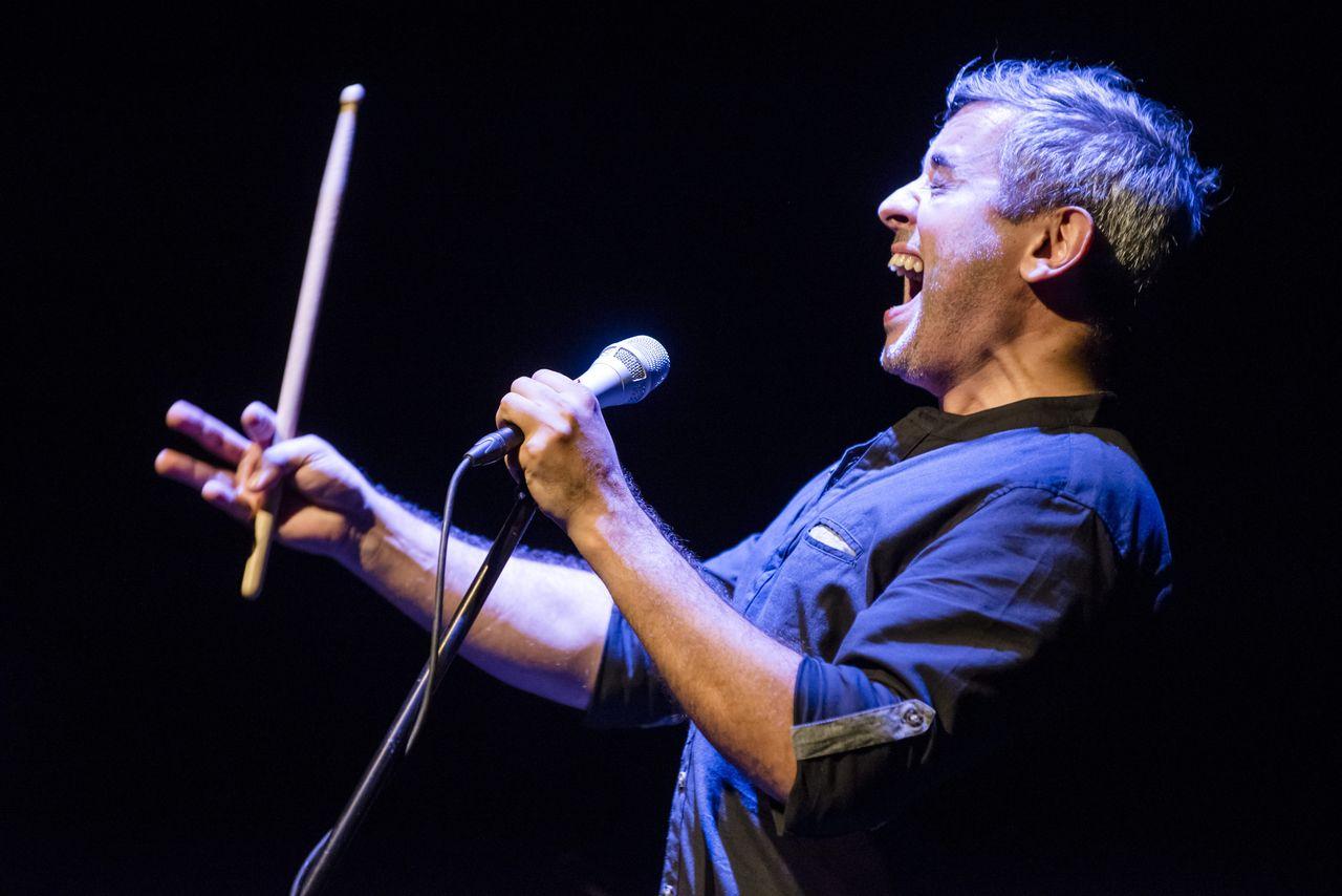 Konrad Imiela ekspresyjnie śpiewa do mikrofonu na statywie. Artystę widać z lewego profilu, lewą reką przytrzymuje mikrofon, prawą unosi do góry pałeczkę do perkusji.