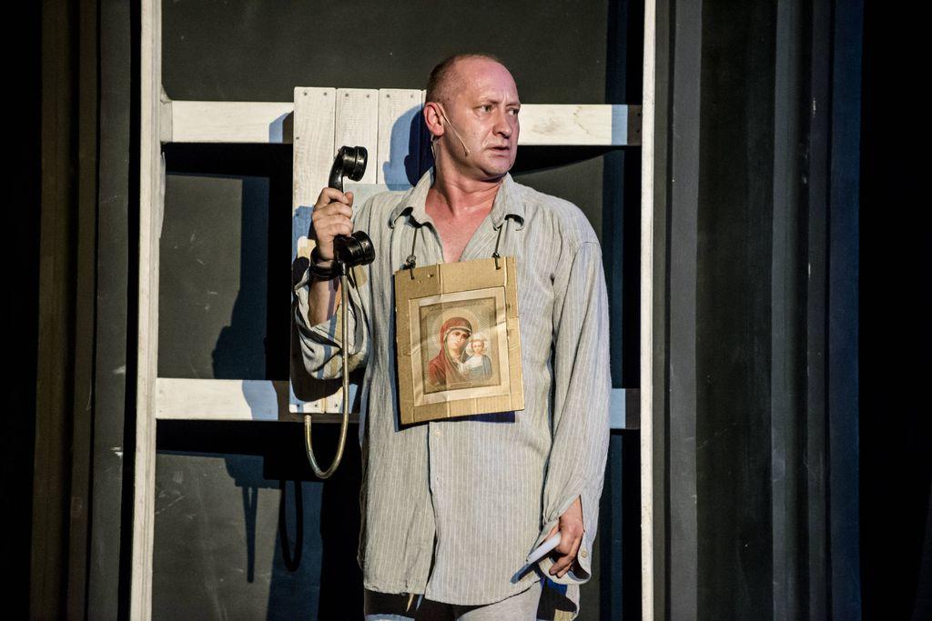 Mężczyzna w jasnej koszuli stoi przy konstrukcji stylizowanej na budkę telefoniczną. Iwan Bezdomny patrzy w prawą stronę, w zgiętej, prawej dłoni trzyma słuchawkę staroświeckiego telefonu. Na szyi ma zawieszony święty obrazek z wizerunkiem Matki Boskiej z Jezusem.