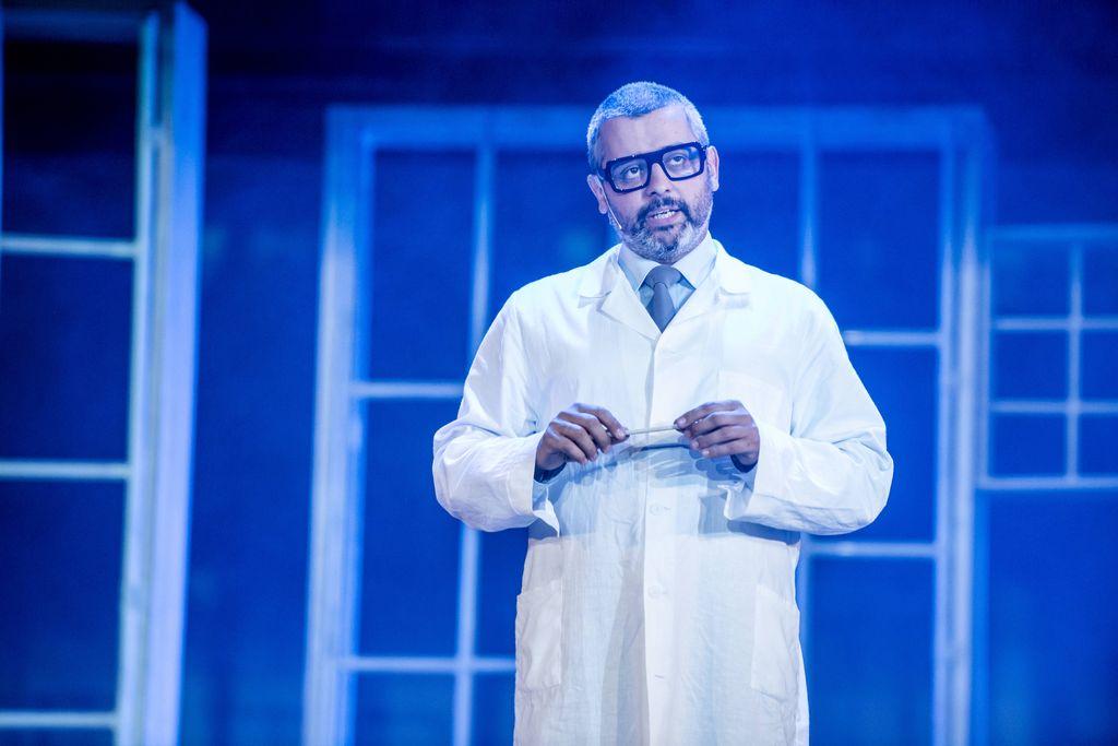 W centrum kadru stoi mężczyzna w białym, lekarskim kitlu. Doktor Strawiński, jest szpakowaty, ma brodę i wąsy, okulary w grubszych, ciemnych oprawkach. Patrzy w dal, trzyma w obu dłoniach, na wysokości klatki piersiowej jakiś długi, wąski przedmiot, być może długopis. W tle za nim – duże ramy okienne.