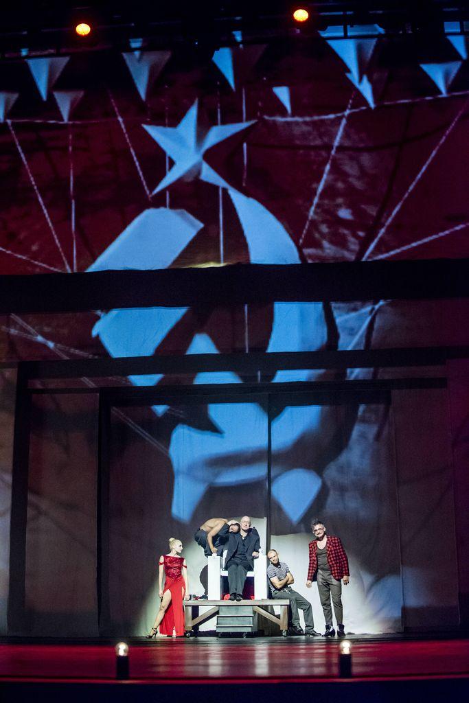 W centrum kadru, w głębi, widać wysoki tron. Siedzi na nim ubrany na czarno Woland, na oparciu tronu przykucnął półnagi Behemot, na podeście przysiadł Asasello. Z prawej strony stoi Korowiow, w okularach, kraciastej, czerwono-czarnej marynarce, szarej koszulce i spodniach. Z lewej strony stoi Hella w czerwonej, wieczorowej sukni z rozcięciami. Nad nimi wyświetlony jest ogromny, niebieski sierp z młotem i pięcioramienną gwiazdą.